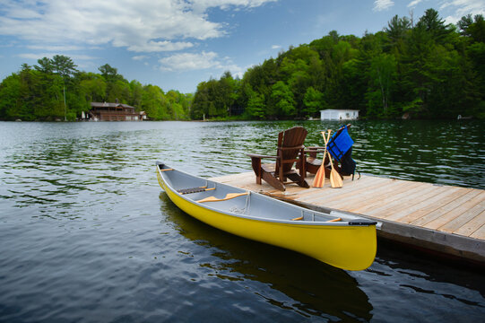 Two Adirondack chairs on a wooden dock facing the blue water of a lake in Muskoka, Ontario Canada. A yellow canoe is tied to the dock. Life jacket and oars are visible near the chairs.