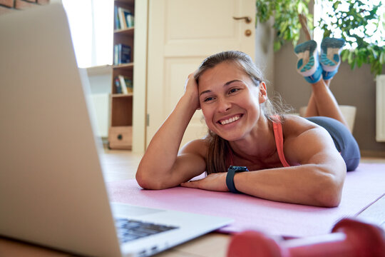 Smiling fit remote yoga fitness trainer, happy young sporty yoga coach teacher lying on mat with laptop at home watching online workout training video on computer. Online fitness tutorial concept.