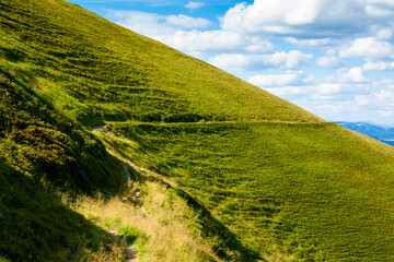 travers path through mountain range. grass on the hills and steep slopes. summer landscape on a sunny day.