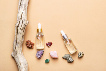 Cosmetic liquid gel products, natural semiprecious stones and old tree snag. Beauty skin care concept
