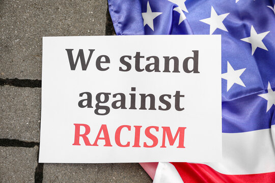 Paper with text WE STAND AGAINST RACISM and flag of USA outdoors