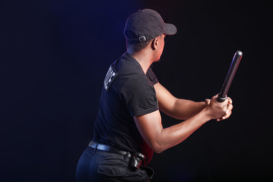 Aggressive African-American police officer with baton on dark background