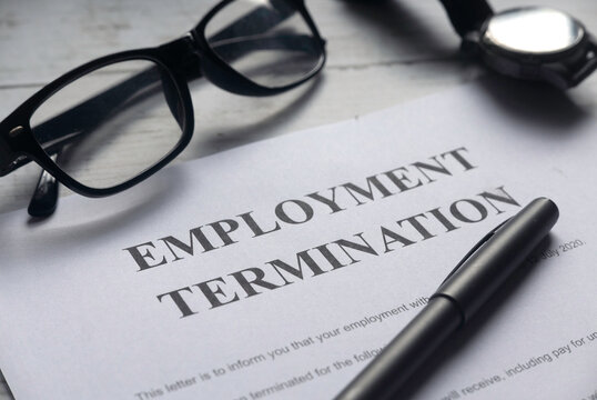Selective focus of glasses,watch,pen and Employment Termination letter on a white wooden background.