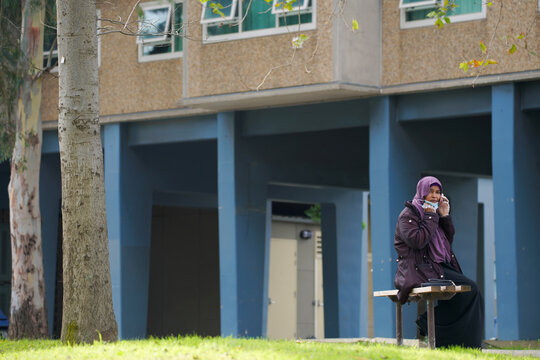 A resident makes a phone call outside a public housing tower, reopened following a COVID-19 lockdown, in Melbourne