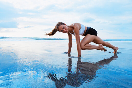 Sporty woman doing mountain climber exercise - run in plank to burn fat. Sunset beach, blue sky background. Healthy lifestyle at tropical island yoga retreat, outdoor activity, family summer vacation.