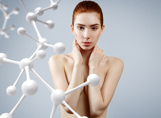 Young woman covering her breasts among molecules chain.