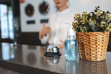 Hand sanitizer bottle on hotel reception desk