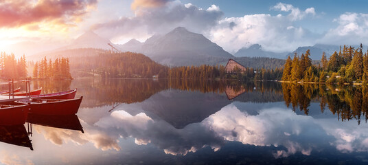 Fotorolgordijn Cappuccino Incredible Nature Landscape. Beautiful view of traditional wooden boats on Strbske Pleso Lake during sunset. Awesome Sunny natural scene. Popular travel and hiking destination. Beautiful on the World