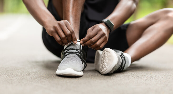 Closeup of black sportsman tying his shoelaces before training