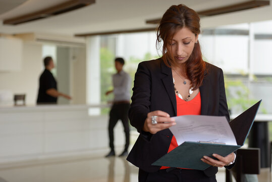 Hispanic businesswoman reading on clipboard in the office building