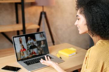 Young woman uses app on laptop for video communication with a diverse multiracial group of coworkers. Virtual meeting, conference, brainstorm