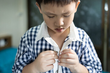 Hand of little child is trying to wear shirt,asian student buttoning his shirt at home,kid boy kindergarten self learning to change clothes dressing before back to school,lifestyle,skills,development