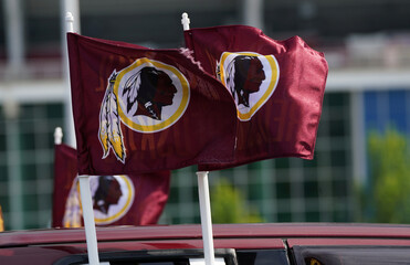 Redskins logos are seen on flags mounted on a vehicle after the team announced they will scrap the name at FedEx Field in Landover, Maryland