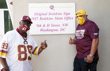 Washington Redskins team employees pose in front of signs after the team announced they will scrap the name and logo at FedEx Field in Landover, Maryland