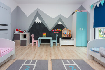 Children bedroom for a boy and a girl with painted mountains on the walls