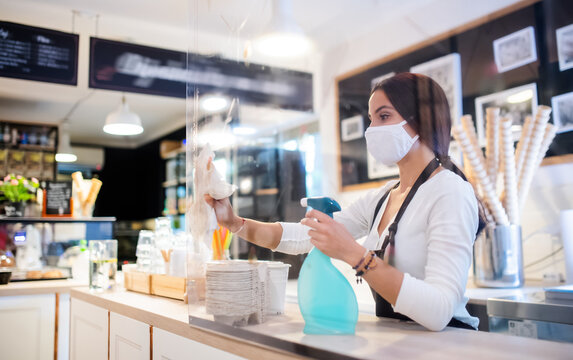 Young woman with face mask working indoors in cafe, disinfecting counter.