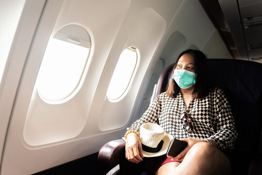 Asian woman with face mask on the airplane.