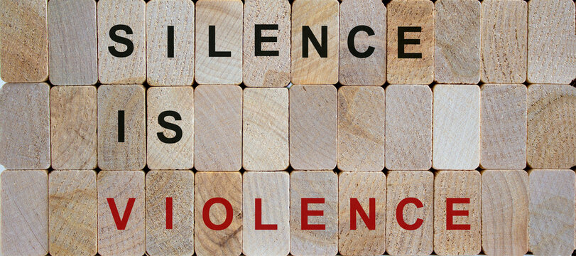 Wooden blocks form the words 'silence is violence'. Beautiful wooden background. Concept image.