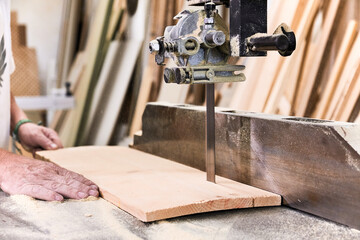Male woodworker in casual clothes focusing and cutting lumber using special electric machine while working in light modern workshop