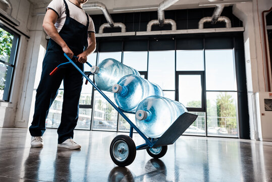 cropped view of delivery man holding hand truck with bottles of purified water