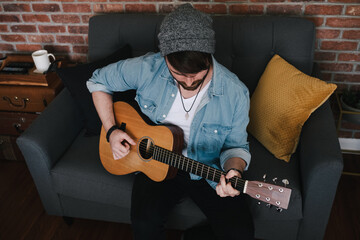 From above bearded guitarist in sock cap and denim jacket playing acoustic guitar while sitting on couch with decorative pillow near brick wall with different musical instruments at home