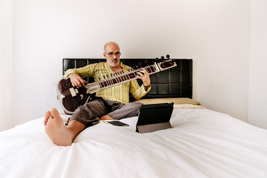 Elderly man sitting on bed with sitar and taking notes in notebook while watching online lesson on tablet