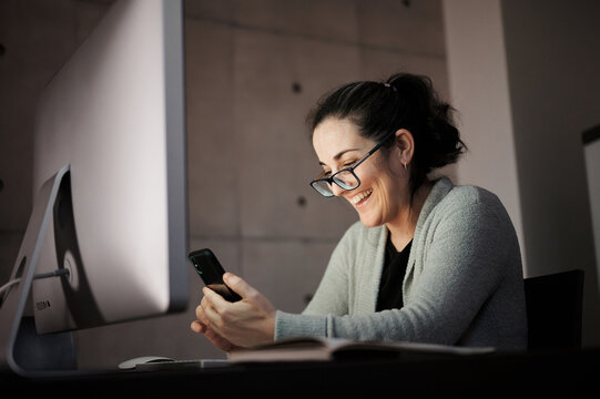 Side view of serious concentrated young female in casual wear and eyeglasses sitting at table with computer with white blank screen and browsing smartphone while working remotely at evening time at home