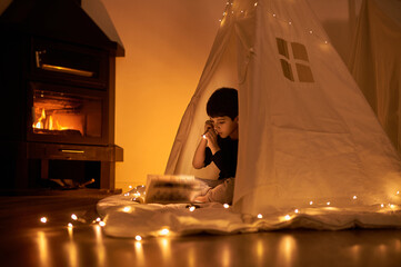 Focused little kid in casual wear reading book while lying in kids play tent with flashlight and garland around near fireplace in apartment