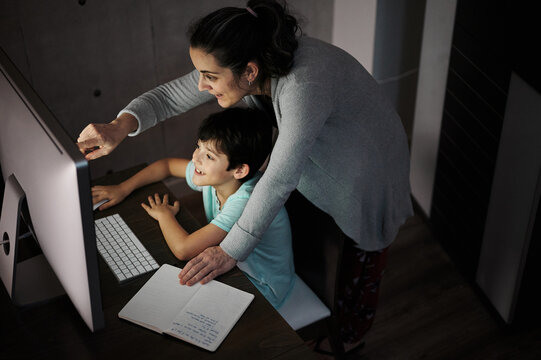 Side view of young woman explaining study task to positive son sitting at table with computer and textbook during online lesson at home
