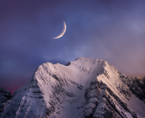 Snowy mountain range peaks under picturesque cloudy pink sky with moon at nightfall in wintertime
