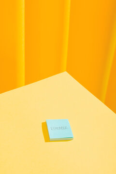 """Little blue post-it with the word """"remember"""" over yellow table"""
