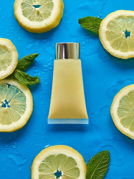Top view of glass bottle surrounded by fresh lemon slices with mint leaves on blue background covered by clear water drops