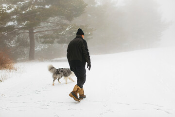 Senior man and his dog walking on a snowy foggy day on the forest