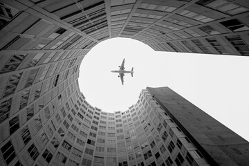 From below of black and white aircraft flying high over modern building with round yard in in city