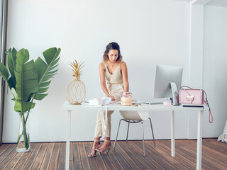 Charming young female in stylish elegant outfit standing near office desk and writing Wall mural