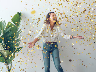 Beautiful young woman in stylish outfit laughing and looking up while standing under?falling golden confetti against white wall Wall mural