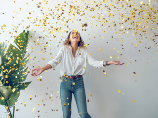 Beautiful young woman in stylish outfit laughing and looking up while standing underfalling golden confetti against white wall