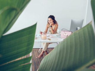 Cute young lady smiling and making notes in notepad while sitting at table in stylish office