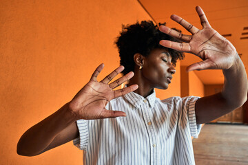 Adult African American female with eyes closed trying to stop negative impact while standing with arms raised against blurred vivid orange interior in corridor of modern building