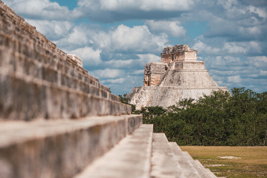 Exterior of stone steps of El Castillo with view of pyramid under cloudy sky in Chichen Itza