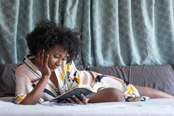 Content African American female in silk robe lying on comfortable bed and enjoying novel while leaning on hand