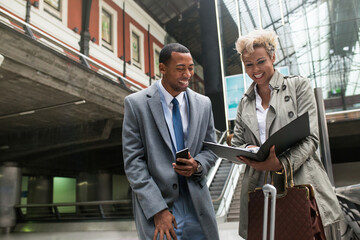 Cheerful laughing black man and woman in trendy elegant clothes having fun while standing with papers on stairs.
