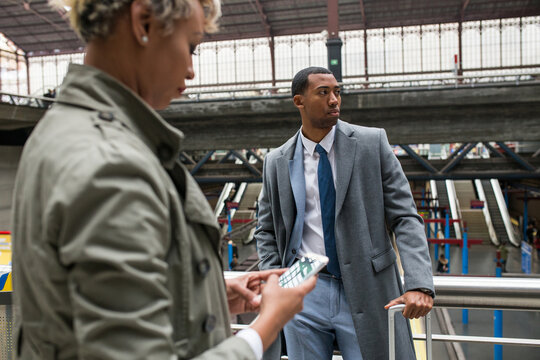 Handsome black man in trendy suit and coat standing with suitcase confidently on train station.