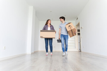 Young couple walking in empty room carrying carton boxes and tool bag