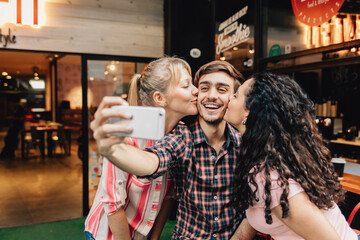Girls kissing a young man taking a selfie