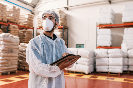 Close up of supervisor in uniform using tablet for checking data while standing in spice factory.