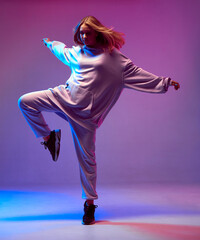 Stylish young girl, cool dancing in a hoodie with developing hair, on a neon background. Dance school poster