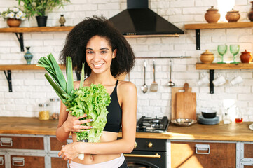Healthy lifestyle concept. Young sporty woman in the kitchen with armful of fresh greenery and salads smiling