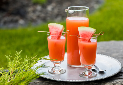 Guava and watermelon juice on a metal tray outside in a park setting.