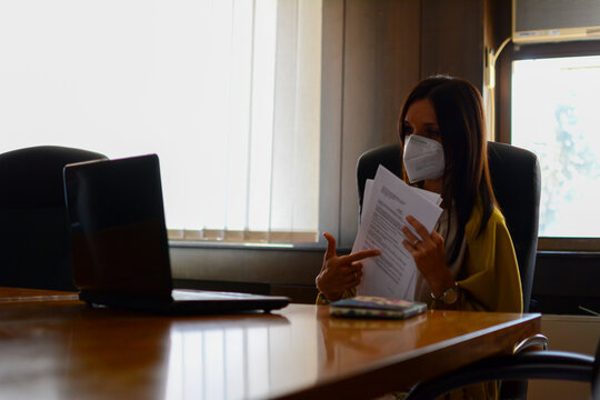 Young woman having video call via laptop in the office. Mid adult Businesswoman Videoconferencing With Her Colleagues On Computer